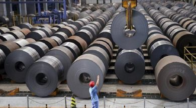 An employee guides a crane as it transports a roll of steel sheet, at a factory in Handan, Hebei