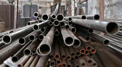 A worker stacks steel pipes in the western Indian city of Ahmedabad