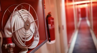 Fire extinguisher and fire hose reel in hotel corridor